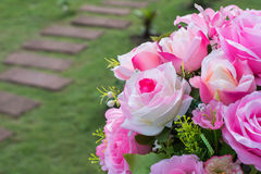 Pink plastic roses in the garden. Decoration on wedding, pink plastic roses in the garden royalty free stock photo