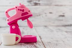 Pink Plastic Toy Machines. Plastic pink kitchen toy machiness on white wooden table Stock Photography