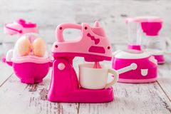 Pink Plastic Toy Machines. Plastic pink kitchen toy machiness on white wooden table Royalty Free Stock Image