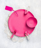 Pink plate with decorative birds and sign on lace doily and gray table Stock Photos