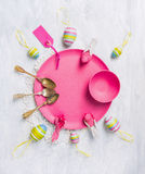 Pink plate with Easter eggs, spoons, ribbons and sign Stock Image