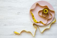 Pink plate with measuring tape over white wooden surface, from above. Flat lay, top view. Copy space. royalty free stock photo