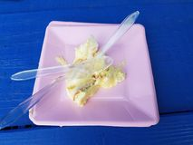 Pink plate with plastic spoons and lemon cake on blue table. A pink plate with plastic spoons and lemon cake on blue table stock photo