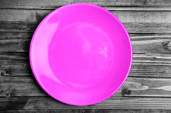 Pink plate on wooden table Royalty Free Stock Photos