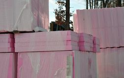 Thermal insulation plates stored at construction site. Pink plates of polymeric material for thermal insulation stacked up at construction site royalty free stock photos