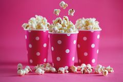 Pink polka dot paper cups with tasty popcorn. stock image