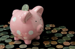 Pink Polka Dot Piggy Bank with Cash. Pink polka dot piggy bank surrounded by cash and coins Stock Images