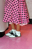 Pink poodle skirt and saddle shoes. Girl is wearing a bright pink with black polka dotted poodle skirt with the slip showing!  Black and white saddle shoes Stock Images