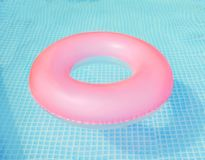 Pink pool float, ring floating in a refreshing blue swimming pool. Aquapark. Inflatable ring floating in pool on sunny day.Summer stock photo