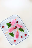 Pink Popsicles with Fruits and Mint on Ice Cubes. Cherry Popsicles and Mint Leaves on a Tray Full of Ice Cubes  on White Backgrund Royalty Free Stock Images