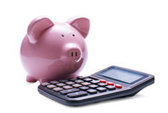 Pink porcelain piggy bank near a desk calculator Stock Photos