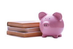 Pink porcelain piggy bank near a pile of old books Stock Images