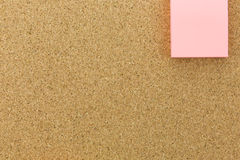 Pink post it on cork board. At the corner Stock Photography