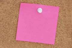 Pink post it note. Pink empty post-it note pinned onto a cork noticeboard Stock Images