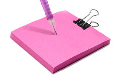 Pink post note pad with clip and pink pen. A side view image of a pink post note pad with clip above and a cropped image of a pink pen isolated on Stock Image