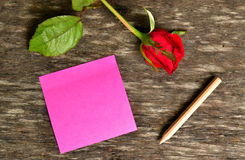 Pink post it note and red rose Royalty Free Stock Images