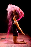 Pink powder dance pose. Dance expression of a girl dancer in a cloud of pink powder coming from her hair Royalty Free Stock Photography