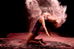 Pink powder hair dance. Dance expression of a girl dancer bending backwards in a cloud of pink powder coming from her hair Royalty Free Stock Photography