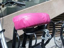Pink protective bike seat cover. Pink waterproof protective bike seat cover royalty free stock photography
