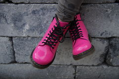 Pink punk alternative girl or woman shoes - cross legged. Nice pink punk alternative girl or woman Military skinhead shoes - cross legged Stock Image