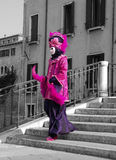 Pink and Purple. A carnival goer poses for photographs at the Venice Carnival Stock Photo