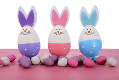 Pink, purple and blue bunny Easter eggs. Pink, purple and blue cute Easter eggs with bunny ears and faces on pink wood table Royalty Free Stock Photo
