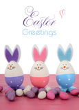 Pink, purple and blue bunny Easter eggs. Pink, purple and blue cute Easter eggs with bunny ears and faces on pink wood table Stock Photo