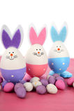 Pink, purple and blue bunny Easter eggs. Pink, purple and blue cute Easter eggs with bunny ears and faces on pink wood table Stock Photos
