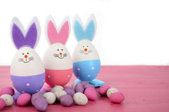 Pink, purple and blue bunny Easter eggs. Pink, purple and blue cute Easter eggs with bunny ears and faces on pink wood table Royalty Free Stock Photography