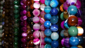 Pink, purple and blue glass beads. Stock Photos
