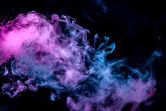 Of pink purple and blue wavy smoke on a black isolated background. Abstract pattern of steam from vape of rising clouds. Of pink purple and blue wavy smoke on a stock photos