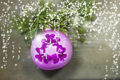 Pink and purple christmas ball with ornament and xmas tree on white wooden background. Winter holiday theme card. Royalty Free Stock Photography