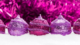 Pink and purple Christmas balls in snow with tinsel Royalty Free Stock Images