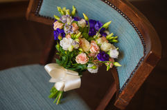 Pink and purple flowers in wedding bridal bouquet on chair Stock Photo