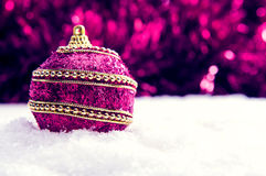 Pink and purple and gold Christmas ball in snow and tinsle, christmas background. Christmas banner with copy space royalty free stock photography