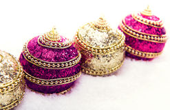 Pink and purple and gold Christmas balls in snow with tinsel, christmas background Royalty Free Stock Image