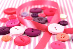 Pink and purple haberdashery buttons and craft ribbon Stock Images
