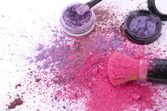Pink and purple makeup powder and brush. Bright pink and purple makeup powder scattered on white table with brush royalty free stock image