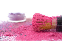 Pink and purple makeup powder and brush. Bright pink and purple makeup powder scattered on white table with brush royalty free stock images