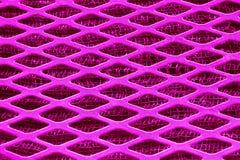 Pink Purple metal lattice lozenge rhombus close-up, under a fine metal grid. Pink Purple metal lattice lozenge rhombus close-up, under a fine metal grid Stock Photo