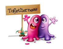 A pink and a purple monster beside a signboard Royalty Free Stock Photo