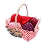 Pink, purple and red yarn with knitting in a basket. Pink, purple and red wool with knitting in a basket, isolated on a white background Stock Image