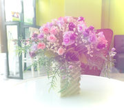 Pink and purple rose flowers in vase on a table. Royalty Free Stock Photo