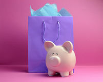 Pink and purple shopping bags with piggy bank - horizontal. Savings, Shopping Sale, End of Season sale, concept with colorful shopping bags against a pink Royalty Free Stock Images
