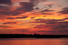 Pink and purple sunrise reflected on the water. Golden sunrise reflected on the water Stock Photo