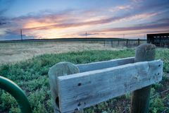 Sunset behind fencing and barn in Eastern Plains Colorado Stock Photo