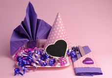 Pink and purple theme party table setting decorations. Against a pale pink background Royalty Free Stock Photo