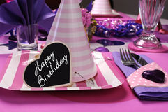 Pink and purple theme party table setting decorations. With party hat closeup and Happy Birthday heart message Royalty Free Stock Photography