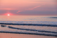 Pink and purple tints with sun peeking over horizon of ocean sunrise Stock Images