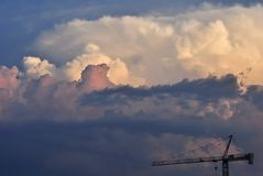 Pink,purple,yellow,white shades of Clouds in a last days of summer. On Florentin sky above some construction works with a crane... the forms of a clouds could royalty free stock images